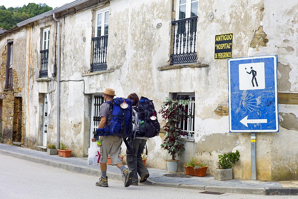 Couple pass sign on Camino de Santiago Pilgrim's Way to Santiago de Compostela at Triacastela in Galicia, Spain