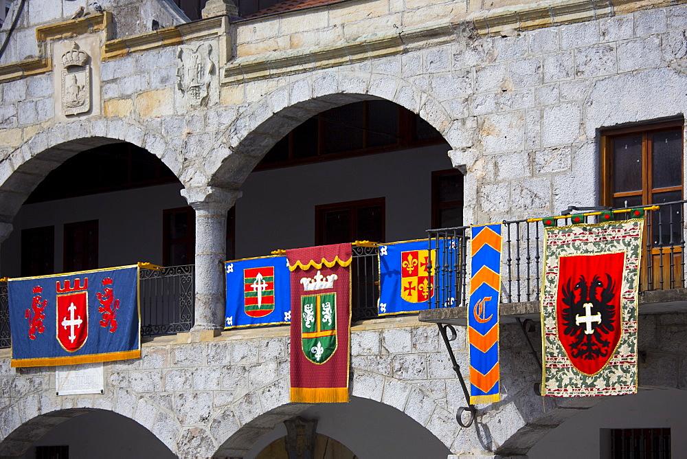 Spanish banners at medieval building in Plaza de la Constitucion 19 March 1812 in Laredo, Cantabria, Spain
