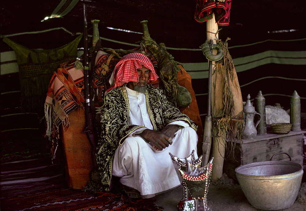 A Bedouin man in his Bedouin tent in the desert at Riyadh in Saudi Arabia. In front is an incense burner.
