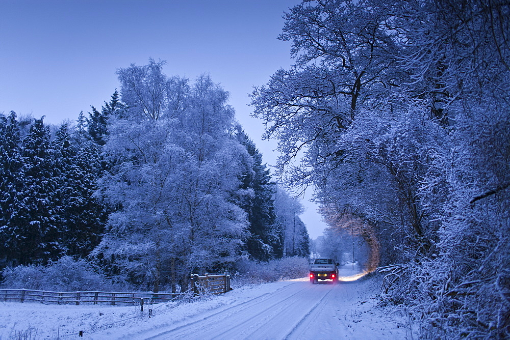 Traditional snow scene with Toyota pick-up truck in The Cotswolds, Swinbrook, Oxfordshire, United Kingdom
