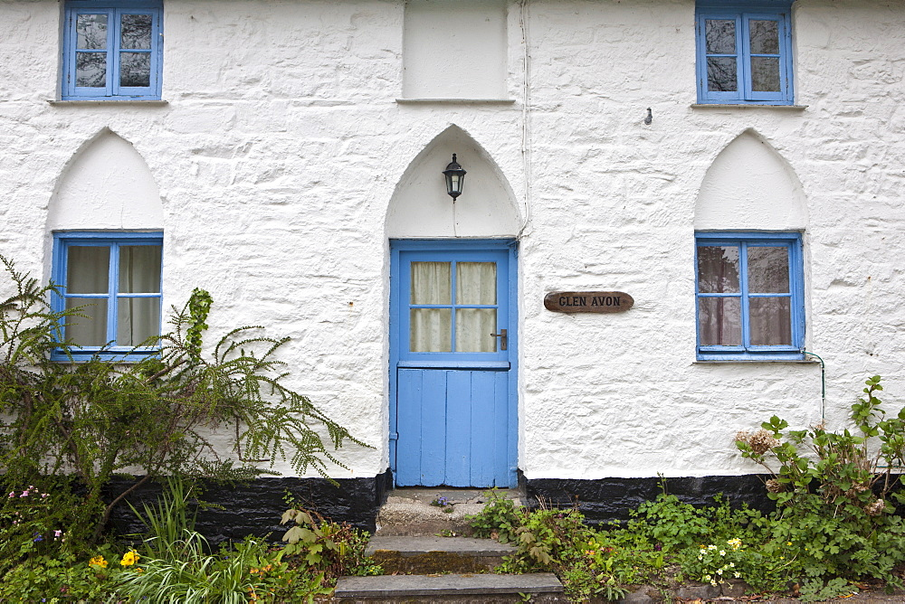 Quaint brightly-painted traditional cottage with gothic style arched door , Cornwall, England, UK
