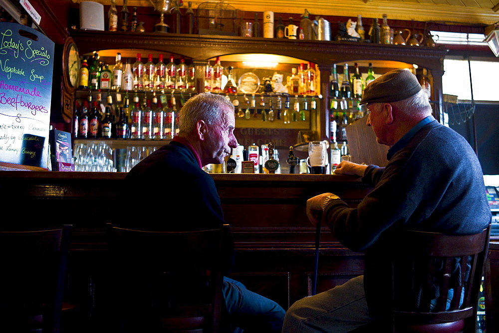 Locals drinking Guinness and beer in traditional Crotty's bar during horse fair, Kilrush, County Clare, West of Ireland