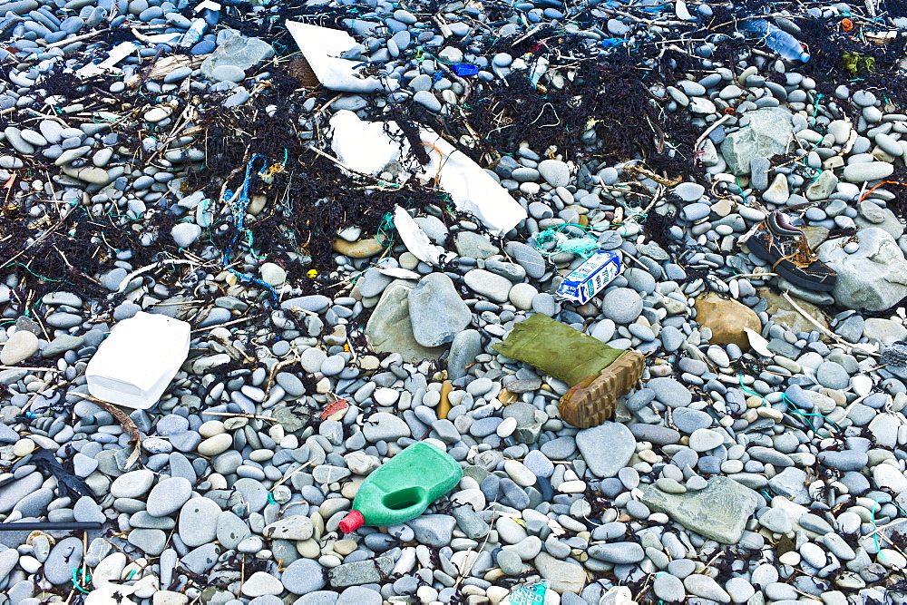 Detritis debris of plastic, and polluting plasticized materials swept in from the sea litter rocks on beach in West Coast of Ireland