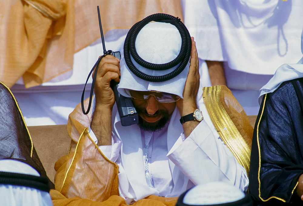 Arab using two-way radio to communicate during parade of armed forces in Abu Dhabi, United Arab Emirates