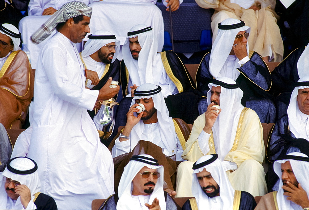 Arab sheikhs drinking coffee and watching parade of armed forces in Abu Dhabi, United Arab Emirates