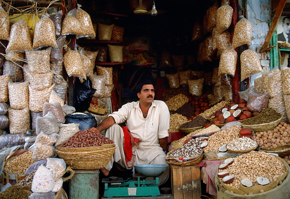 A man in Islamabad, Pakistan working in his shop selling fruit and nuts