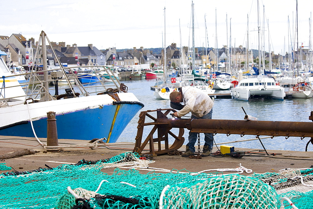 Welder at work at boatyard at Channel port of St Vaast La Hougue in Normandy, France