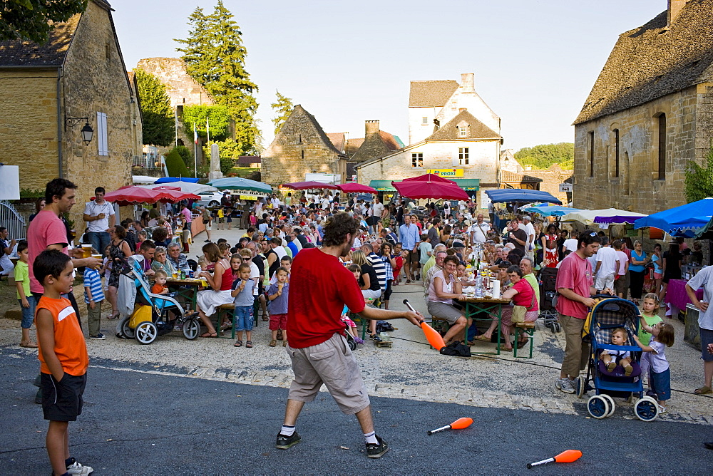 Juggler at village fete traditional festival in St Genies in the Perigord region,  France