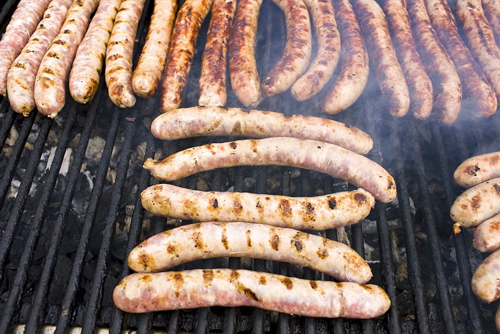Barbecued sausages saucissons being cooked on griddle for sale as snack food at farmers market in Normandy, France - 1161-7744