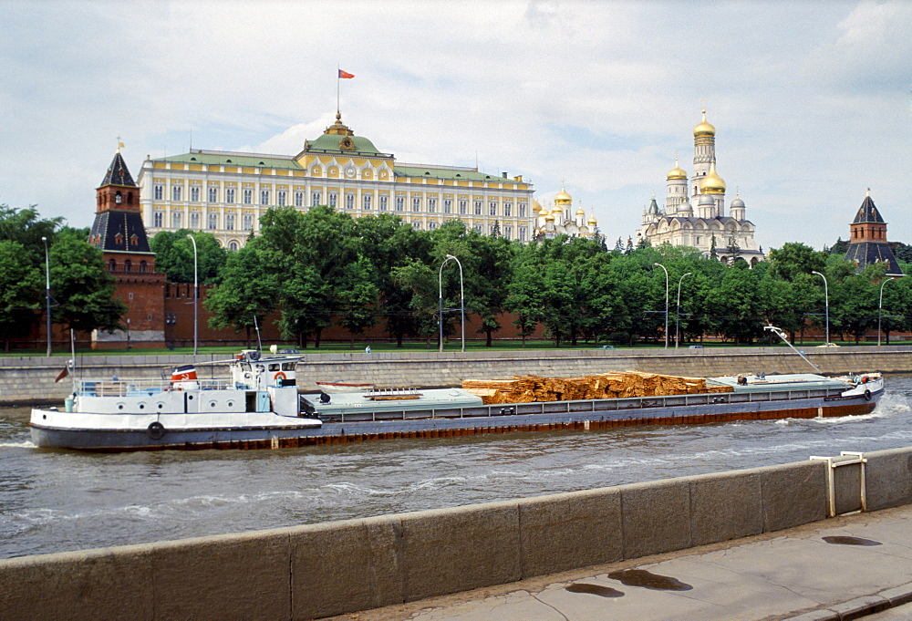 Cargo of logs passes The Kremlin and Moscow River, Russia
