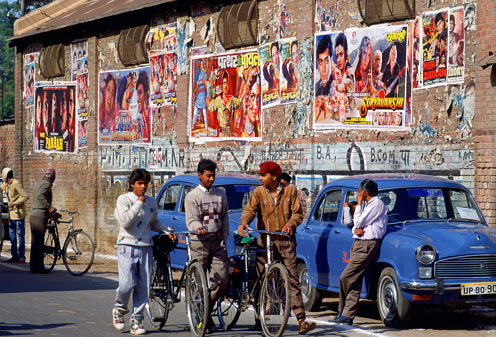 ' Bollywood ' film posters advertising the latest movies in Agra, India.  Young men chatting together while pushing their bicycles.