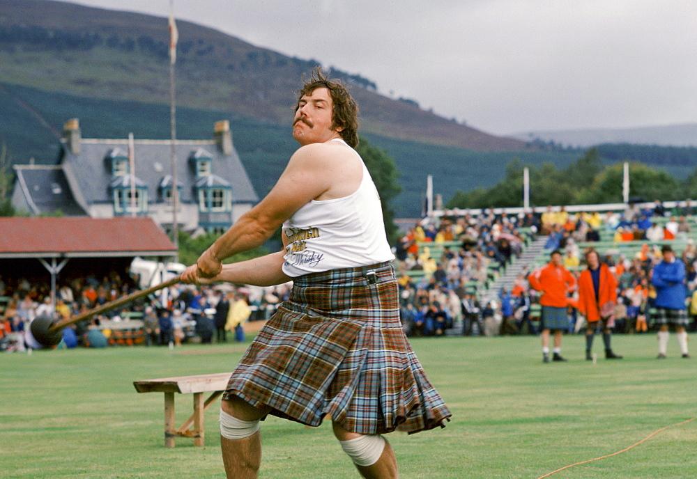 Scottish strongman in tartan kilt tossing the hammer at the Braemar Royal Highland Gathering, the Braemar Games in Scotland