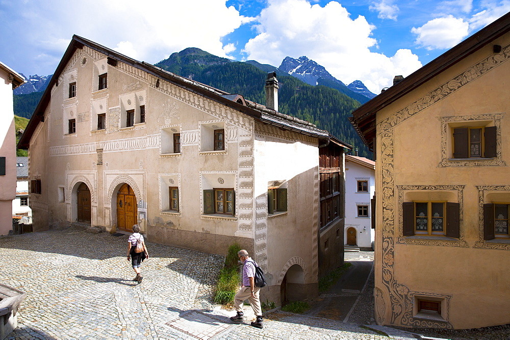 Tourists stroll in the Engadine Valley in village of Ardez with restored painted stone 17th century houses, Graubunden, Switzerland, Europe