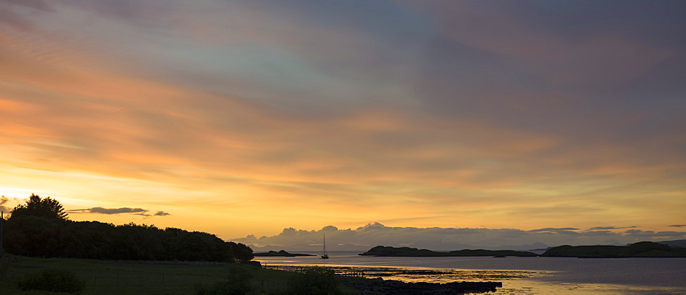 A solitary boat at sunset in Dunvegan Loch, a sea loch on the Isle of Skye, Western Isles, Inner Hebrides, Scotland, United Kingdom, Europe