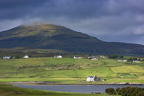 White croft cottages nestled in hamlet by mountain and Loch Vatten under grey clouds at Roag, Isle of Skye, Inner Hebrides and Western Isles, Scotland, United Kingdom, Europe