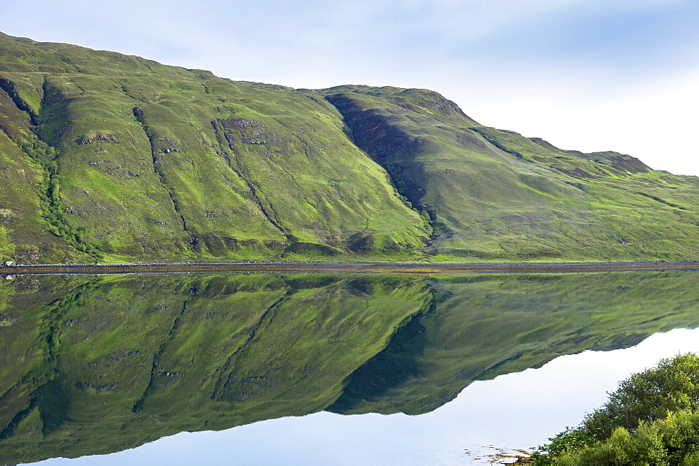 Mountain slopes reflected in the waters of a loch, Isle of Skye, Inner Hebrides, Highlands and Islands, Scotland, United Kingdom, Europe