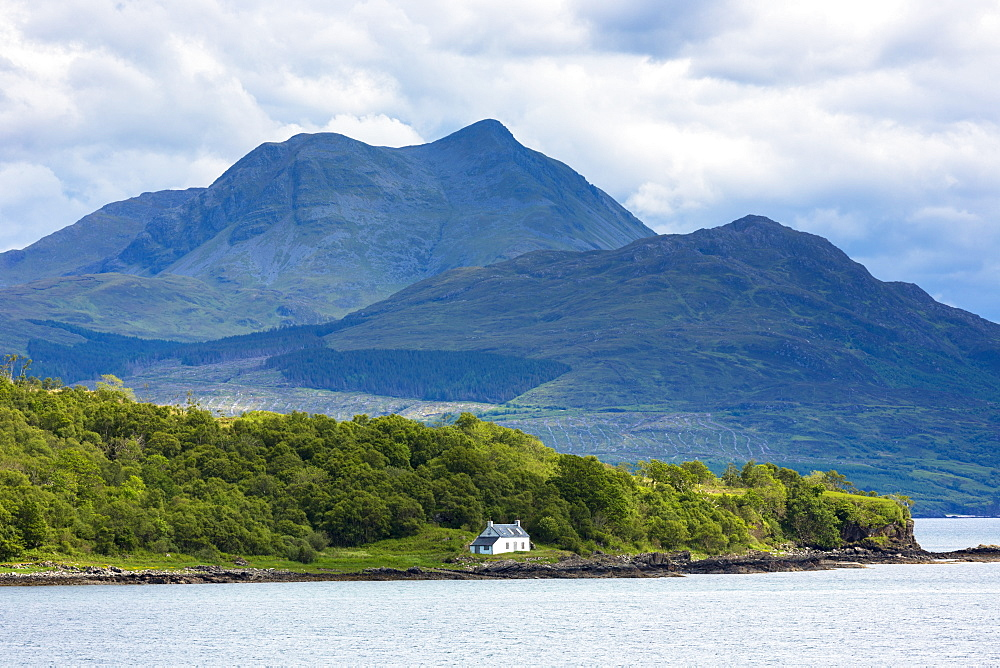 Solitary whitewashed croft cottage across the Sound of Sleat with Knoydart mountain behind, Isle of Skye, Inner Hebrides and Western Isles, Scotland, United Kingdom, Europe