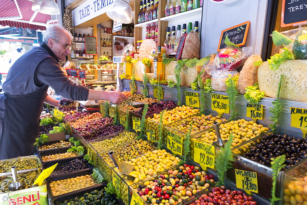 Shopkeeper with green and black olives for sale at food market in Kadikoy district on Asian side of Istanbul, Turkey, Asia Minor, Eurasia