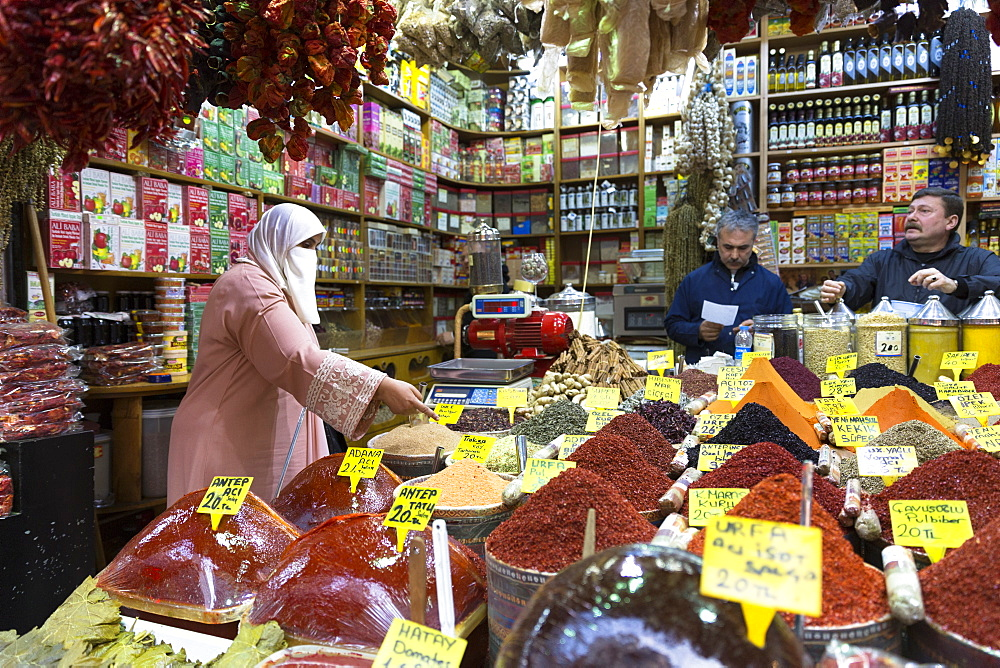 Woman shopper wearing Muslim veil buys spices in Misir Carsisi Egyptian Bazaar food and spice market, Istanbul, Turkey, Europe