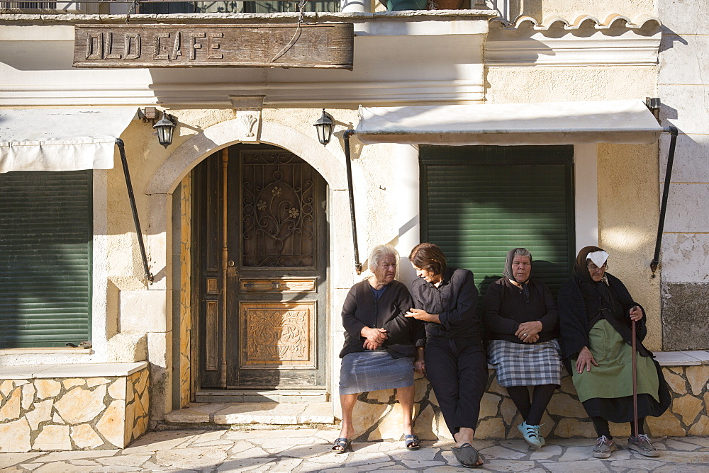 Elderly Corfiot women wearing traditional black clothes sitting relaxing in village square of Krini, Corfu, Greek Islands, Greece, Europe - 1161-8665