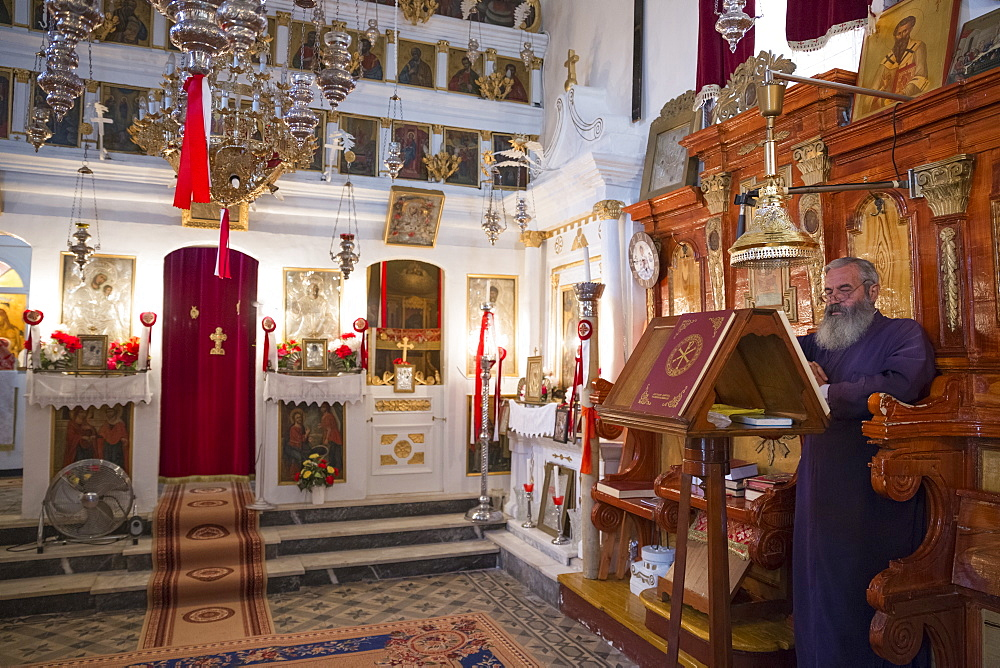 Greek Orthodox priest reading Bible inside chapel of Christian church at Krini, Corfu, Greek Islands, Greece, Europe