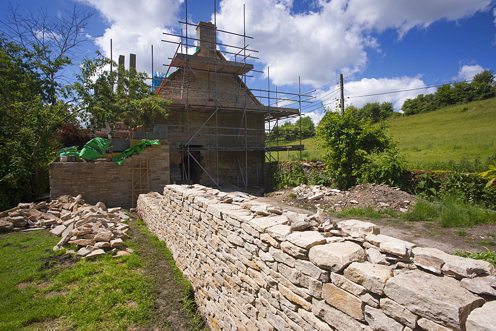 Home improvement, cottage renovation and newly built dry stone wall constructed of new Cotswold stone by traditional methods at period property, Swinbrook, Oxfordshire, Cotswolds, England, United Kingdom, Europe - 1161-8689