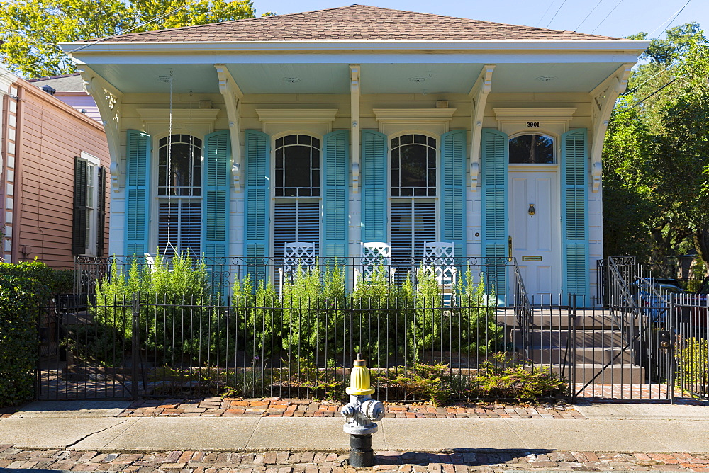 Traditional bright color clapboard cottage house in the Garden District of New Orleans, Louisiana, USA