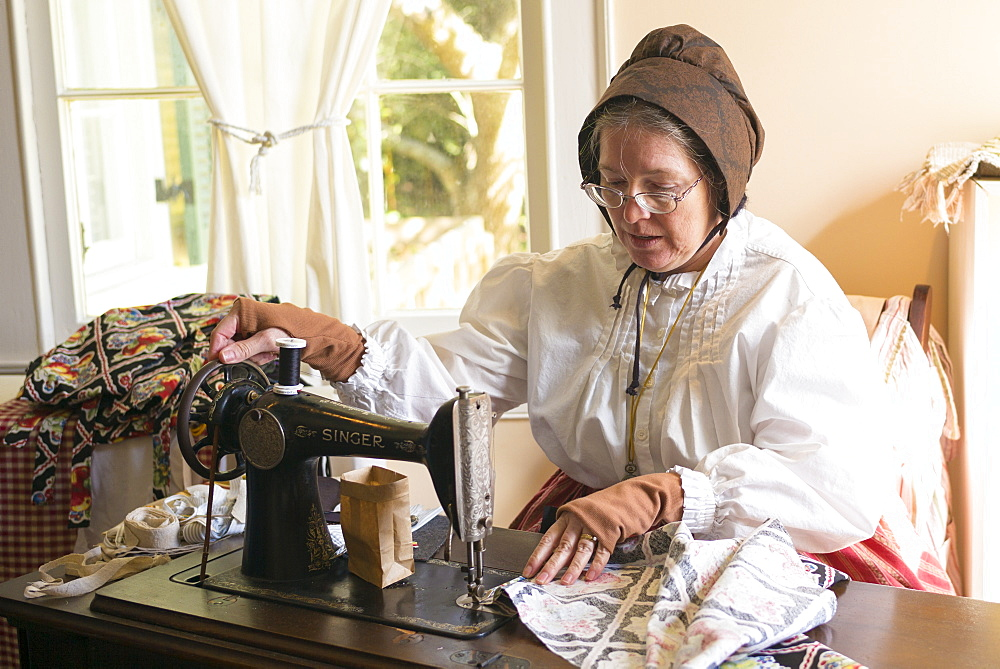 Craftsperson with sewing machine at Vermilionville history museum of Acadian, Creole, Native American cultures, Louisiana, USA - 1161-8742