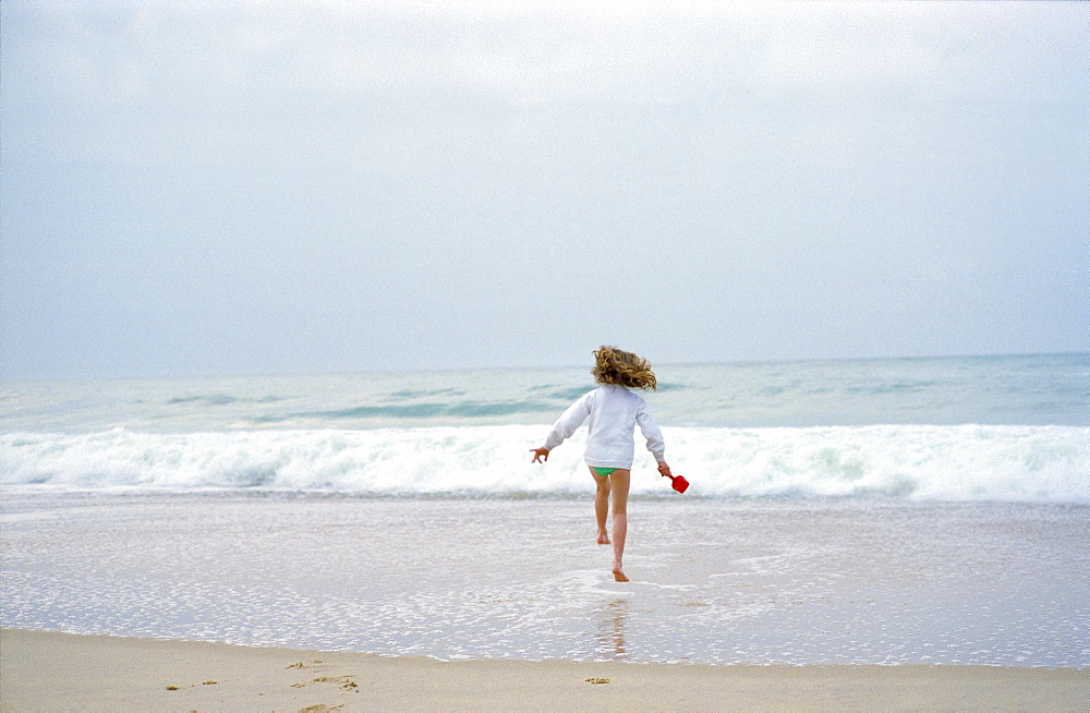 An eight year old girl running into the sea in France