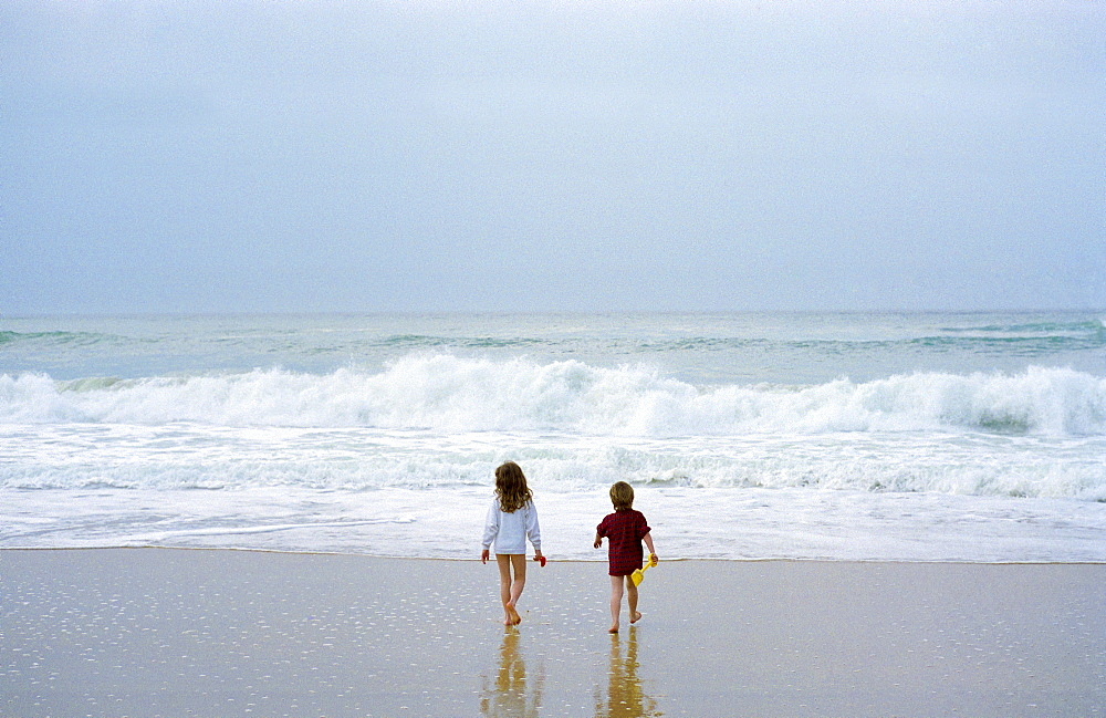 An eight year old girl and six year ld boy walking ino the sea in France
