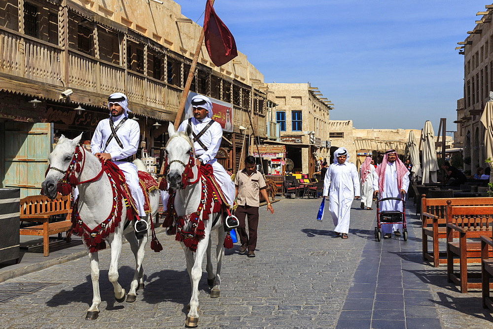Busy street scene with traditionally dressed mounted policemen and shoppers, Souq Waqif, Doha, Qatar, Middle East