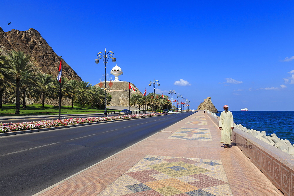 Man wearing dishdasha walks along Mutrah Corniche with national flags, flower beds and Giant Incense Burner, Muscat, Oman, Middle East
