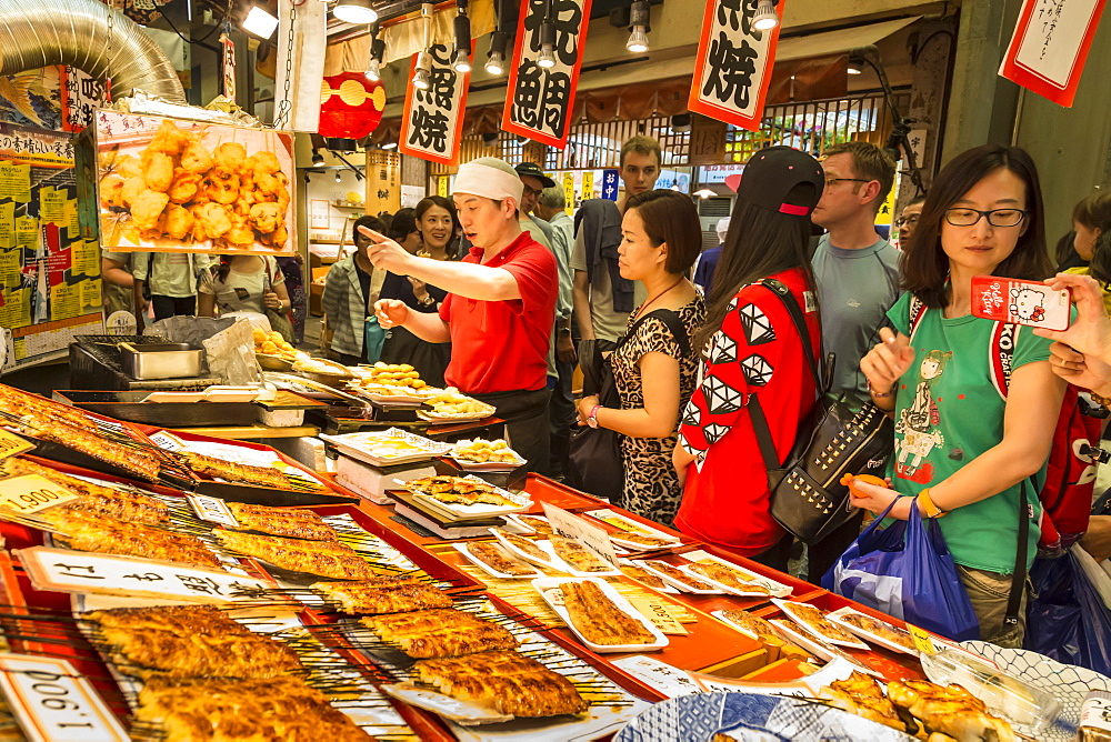 Customers queue at busy local Japanese teriyaki food stall, Nishiki Market (Kyoto's Kitchen), Downtown Kyoto, Japan, Asia