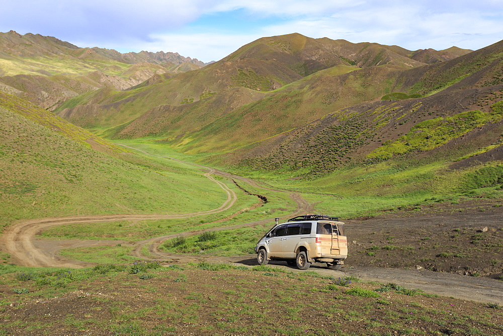 Vehicle travels off road through lush mountains, Gurvan Saikhan National Park, near Yolyn Am (Yol Valley), Gobi Desert, Mongolia, Central Asia, Asia