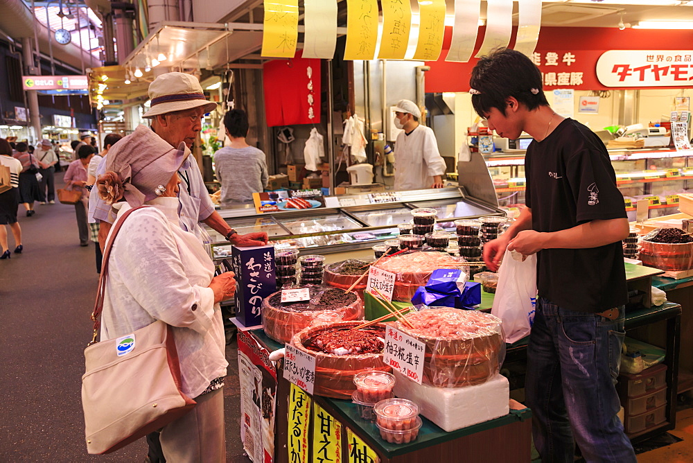 Shoppers make purchase at Omicho fresh food market, busy and colourful covered streets lined by stalls, Kanazawa, Japan, Asia