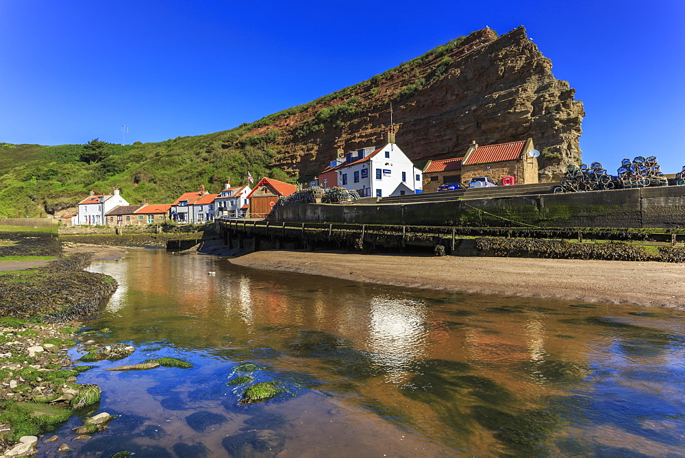 Harbour cottages beneath steep cliffs, fishing village, low tide in summer, Staithes, North Yorkshire Moors National Park, Yorkshire, England, United Kingdom, Europe
