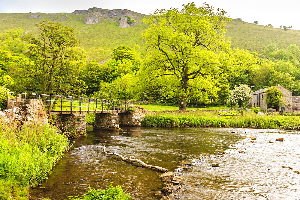 Bridge across River Wye, stone farm buildings, Monsal Dale, spectacular limestone scenery, Peak District, Derbyshire, England, United Kingdom, Europe