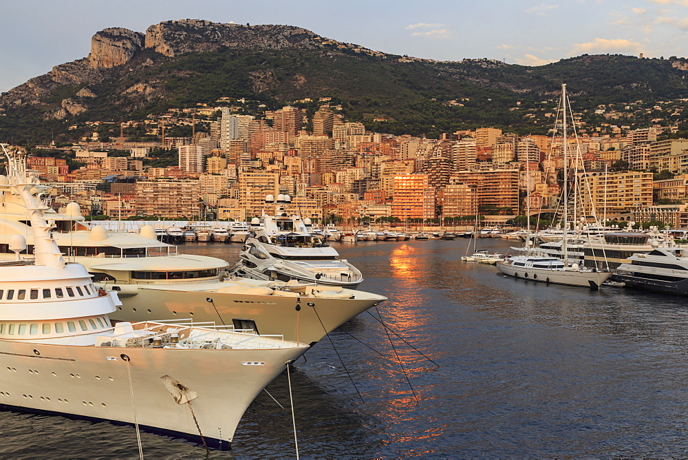Huge super yachts in the glamorous Port of Monaco (Port Hercules) at sunrise, from the sea, Monte Carlo, Monaco, Mediterranean, Europe