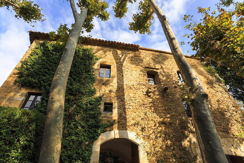 Gala Dali Castle Museum facade amidst tall trees, medieval home of Salvador Dali, Pubol, Baix Emporda, Girona, Catalonia, Spain, Europe