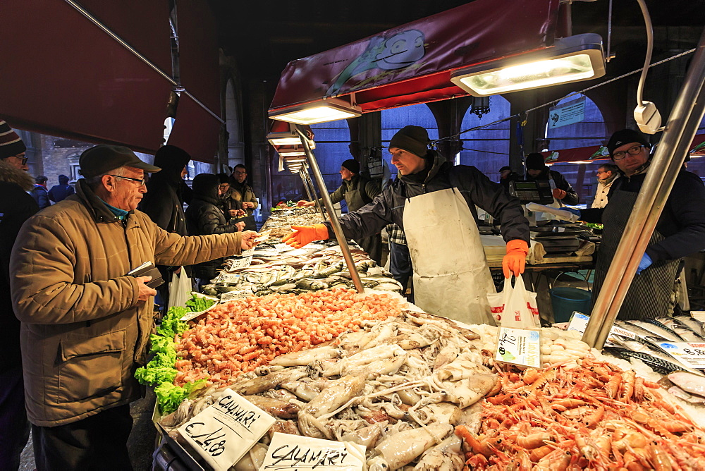 Customer pays for purchase, busy fish stall in winter, Pescheria, Rialto Market, Venice, UNESCO World Heritage Site, Veneto, Italy, Europe