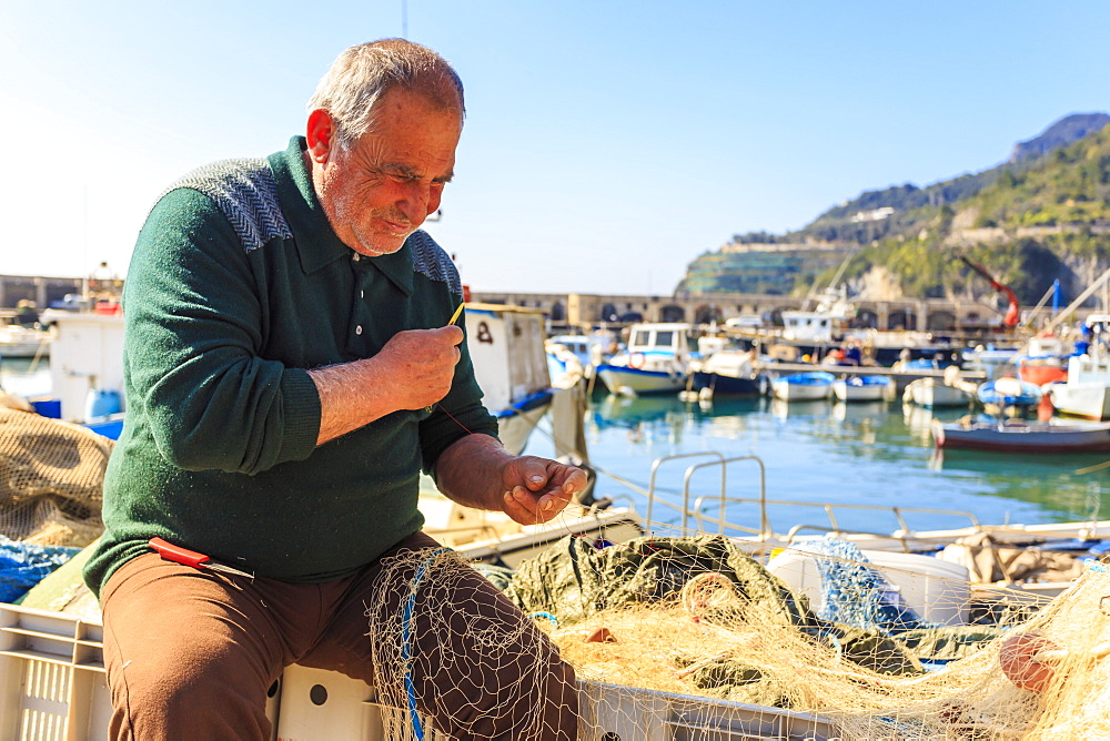 Stock photo of Fisherman mending nets at Cetara harbour