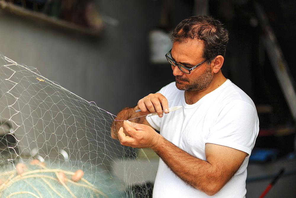 Marina Corricella, fisherman carefully mends fishing nets, Procida Island, Bay of Naples, Italy - 1167-1374