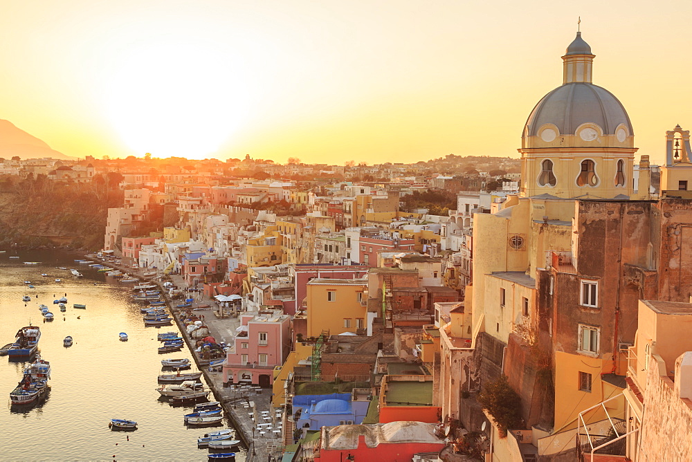 Marina Corricella at sunset, fishing village, colourful fishermen's houses, boats and church, Procida Island, Bay of Naples, Campania, Italy, Europe