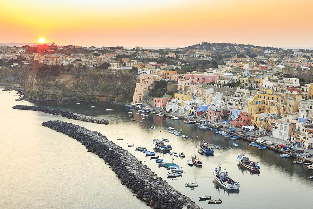 Marina Corricella sunset, fishing village, colourful fishermen's houses, boats and church, Procida Island, Bay of Naples, Campania, Italy, Europe
