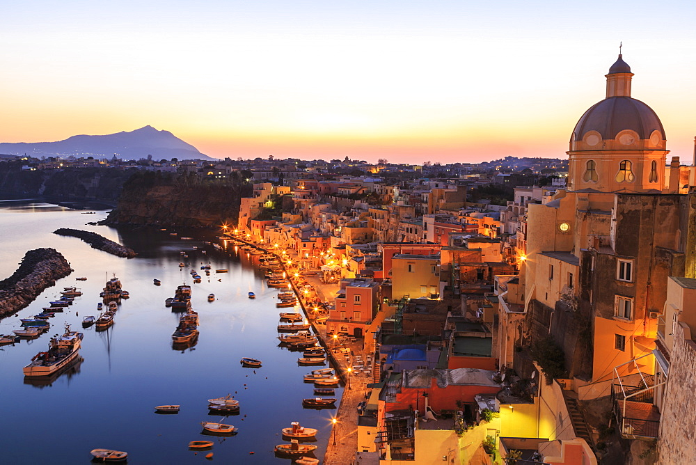 Marina Corricella, blue hour after sunset, fishing village, colourful houses, boats and church, Procida, Bay of Naples, Campania, Italy, Europe