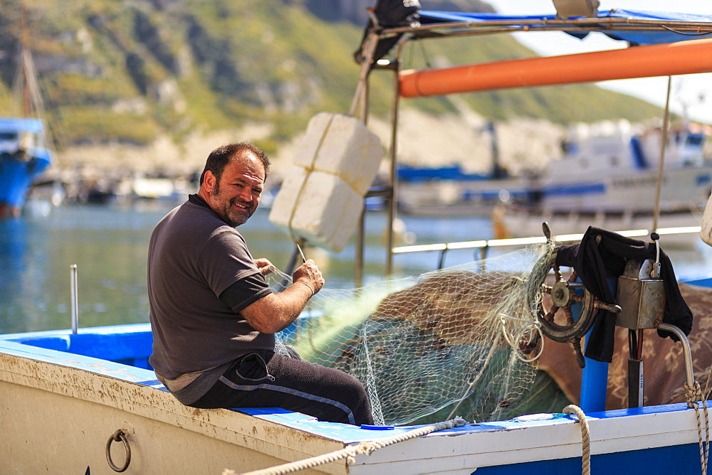 Marina Corricella harbour, smiling fisherman mending fishing nets on a boat, Procida Island, Bay of Naples, Campania, Italy