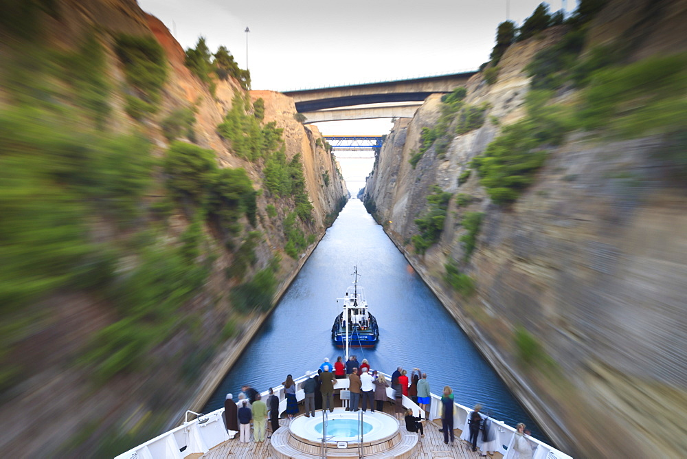 Tourists on the bow of a small cruise ship being pulled by a tug, early morning transit of Corinth Canal, Greece, Europe