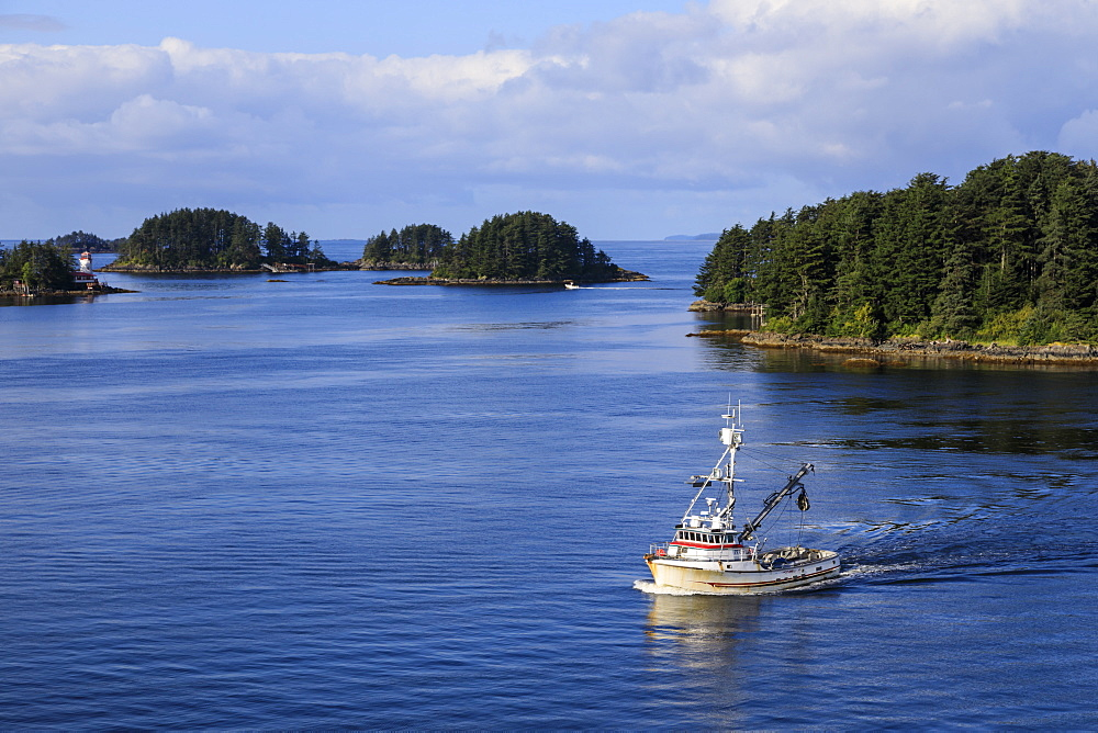 Commercial fishing boat and small forested islands, rare Summer sun, Sitka Sound, Sitka, Baranof Island, Southeast Alaska, USA