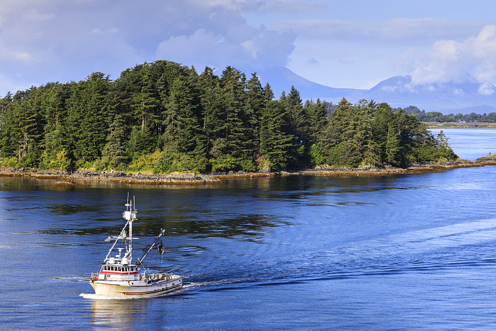 Commercial fishing boat and small forested island, rare Summer sun, Sitka Sound, Sitka, Baranof Island, Southeast Alaska, USA