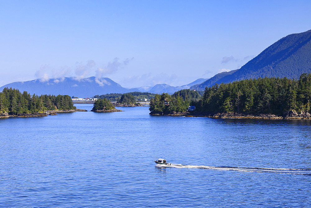 Boat travels through small forested islands, clearing morning mists, rare Summer sun, Sitka Sound, Sitka, Southeast Alaska, United States of America, North America